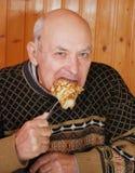 El abuelo se sentó en una tabla y come la crepe caliente con apetito fotografía de archivo libre de regalías