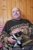 El abuelo se sienta en un sofá en la dacha y plancha el gato que se sienta en él en un revestimiento foto de archivo libre de regalías