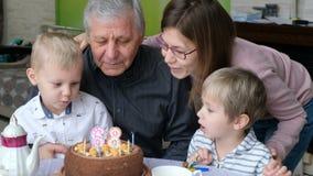 El abuelo sopla hacia fuera velas de la torta de cumpleaños en el partido de la familia, celebrando cumpleaños almacen de metraje de vídeo