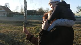 El abuelo y la abuela con su nieto caminan en el parque y hablan en el teléfono móvil con sus parientes en almacen de metraje de vídeo