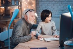 El abuelo y el nieto están jugando a juegos en el ordenador en la noche en casa El abuelo está animando para el muchacho fotos de archivo