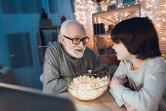 El abuelo y el nieto están mirando película con palomitas en la noche en casa Foto de archivo libre de regalías