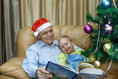 El abuelo y el nieto leyeron un cuento de hadas de la Navidad Imagenes de archivo