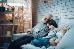 El abuelo y el nieto son el sentarse el dormir en la noche en casa Foto de archivo