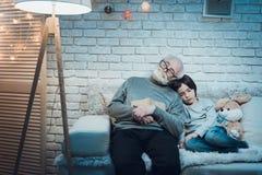 El abuelo y el nieto son el sentarse el dormir en la noche en casa Foto de archivo libre de regalías