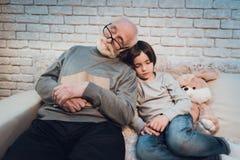 El abuelo y el nieto son el sentarse el dormir en la noche en casa imágenes de archivo libres de regalías