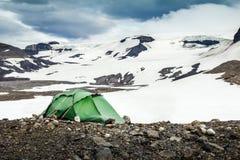 El acampar con la tienda Glaciares de la montaña Nevado y viento de tormenta islandia Foto de archivo libre de regalías