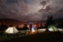 El acampar de la noche El par romántico que se coloca y que se sostiene da la elevación para arriba Foto de archivo