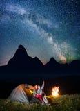 El acampar de la tienda de la noche Caminantes felices de los pares que se sientan cerca de la tienda y de la hoguera y que gozan Imagenes de archivo