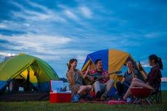 El acampar de viajeros jovenes asiáticos felices en el lago Imágenes de archivo libres de regalías
