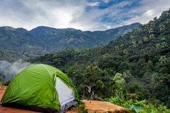 El acampar en bosque con la opinión de la tienda y del bosque de la tabla que se sienta foto de archivo
