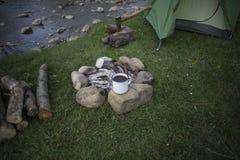 El acampar en el bosque en los bancos del río Imágenes de archivo libres de regalías
