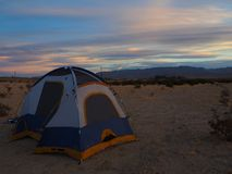 El acampar en las montañas en la puesta del sol fotografía de archivo