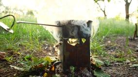 El acampar en el pote del bosque A de comida está hirviendo en la estufa El humo viene del fuego almacen de video