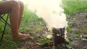 El acampar en el pote del bosque A de comida está hirviendo en la estufa El humo viene del fuego almacen de metraje de vídeo