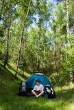 El acampar: Lectura del hombre joven Fotos de archivo libres de regalías
