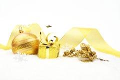 El acebo de oro de la Navidad deja el regalo en nieve Imágenes de archivo libres de regalías
