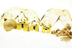 El acebo de oro de la Navidad deja los regalos en nieve Imágenes de archivo libres de regalías