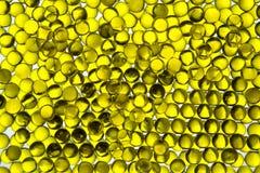 El aceite de linaza en cápsulas amarillas brillantes contornea el foco selectivo ligero imágenes de archivo libres de regalías