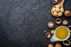 El aceite de nuez de macadamia y la nuez de macadamia pelada fotos de archivo libres de regalías