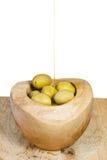 El aceite de oliva en chorrito fino fluye en aceitunas en cuenco fotografía de archivo libre de regalías
