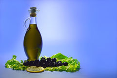 El aceite de oliva en una botella transparente, aceitunas se ennegrece con un limón y Fotos de archivo libres de regalías