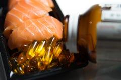 El aceite de pescado con las píldoras del aceite de pescado pored del envase aislado Fotografía de archivo