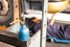 El aceite viejo puede en el garaje con el mecánico del motor Fotografía de archivo