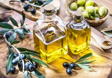 El aceite y las bayas de oliva están en la bandeja de madera verde oliva imagenes de archivo