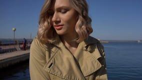 El acercamiento a la mujer rubia joven atractiva en foso con la maleta del vintage se está sentando en el embarcadero de Jacht metrajes