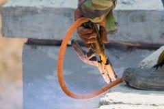 El acero de soldadura del hombre del soldador obstruye el apoyo del muro de cemento prefabricado, del trabajador con desprotegido fotos de archivo