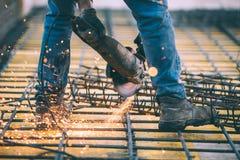 El acero industrial del corte del ingeniero de construcción usando el inglete del ángulo vio, amoladora y las herramientas Fotografía de archivo libre de regalías