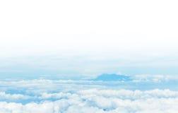 El acodar de nubes y de moutain en el fondo blanco del cielo Foto de archivo