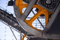 El acoplamiento industrial con la naranja viaja en tranvía la rueda volante con protector yo Foto de archivo libre de regalías