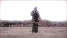 el Acosador-vagabundo vaga a través del desierto con cosas encontradas y una ballesta El mundo se sumerge en la era poste-nuclear almacen de metraje de vídeo
