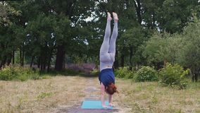 El acróbata de sexo femenino realiza el soporte de la mano al aire libre, las manos fuertes del ejercicio de la balanza lentas almacen de metraje de vídeo