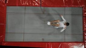 El acróbata del gimnasta de la visión superior en la ropa blanca realiza una voltereta en un trampolín en la cámara lenta almacen de video