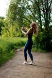 El activar de funcionamiento del corredor de la mujer en el parque del verano, agitando su pelo Imagen de archivo