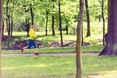 El activar de funcionamiento del corredor de la mujer en parque y bosque verdes del verano Imagen de archivo libre de regalías