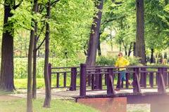 El activar de funcionamiento del corredor de la mujer en parque y bosque verdes del verano Foto de archivo