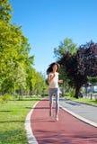 El activar hermoso de la chica joven al aire libre a lo largo del camino de los árboles Imagen de archivo libre de regalías