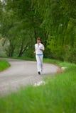 El activar - mujer juguetona que se ejecuta en el camino en naturaleza Fotos de archivo libres de regalías
