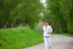 El activar - mujer juguetona que se ejecuta en el camino en naturaleza Fotografía de archivo