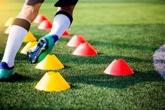 El activar y salto del jugador de fútbol entre los marcadores del cono en arte verde foto de archivo libre de regalías