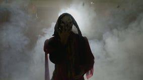 El actor asustadizo se vistió en un traje espantoso de Halloween que hacía los movimientos fantasmagóricos con las manos - almacen de metraje de vídeo