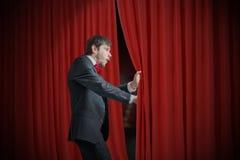 El actor o el ilusionista curioso está mirando detrás de la cortina roja y se sorprende imagen de archivo libre de regalías