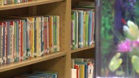 El acuario cerca de los libros de niños en biblioteca deja de lado (2 de 2) metrajes