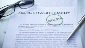 El acuerdo de fusión aprobado, sello selló en el documento oficial, contrato del negocio foto de archivo