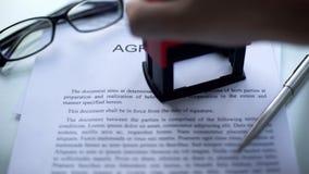 El acuerdo, funcionarios da el sellado del sello rectangular en el documento de negocio imagen de archivo libre de regalías