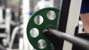 El adición del hombre pesa las placas a la barra olímpica entre los sistemas de sistemas de pecho de la prensa del empuje metrajes